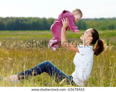Happy young mather play with smiling baby and throw upwards on nature - stock photo