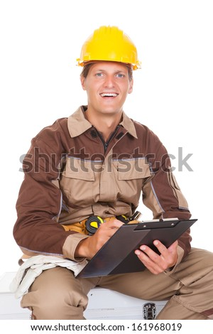 Happy Young Mechanic In Protective Workwear Writing On Clipboard - stock photo