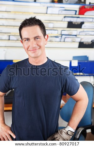Happy young mechanic looking at the camera - stock photo