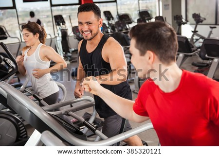 Happy young men bumping their fists while doing some jogging on a treadmill at the gym - stock photo