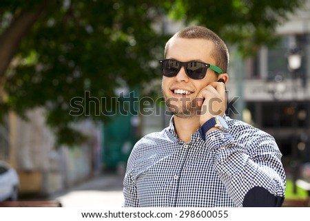 Happy young men calling by phone in summer street - stock photo