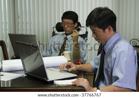 Happy young men working with laptop in the office - stock photo
