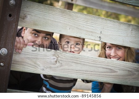 Happy Young Mixed Race Ethnic Family Looking Through a fence In The Park. - stock photo