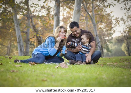 Happy Young Mixed Race Ethnic Family Playing Together with Bubbles In The Park. - stock photo