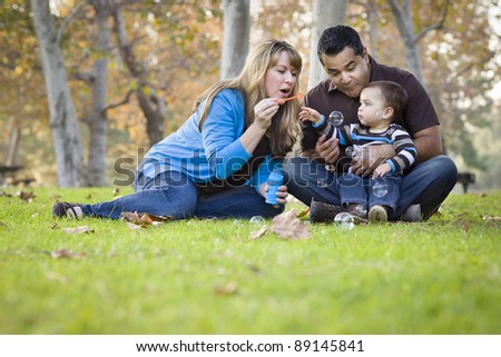 Happy Young Mixed Race Ethnic Family Playing with Bubbles In The Park. - stock photo