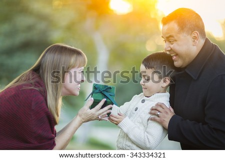 Happy Young Mixed Race Son Handing Gift to His Mom As Father Stands Behind. - stock photo