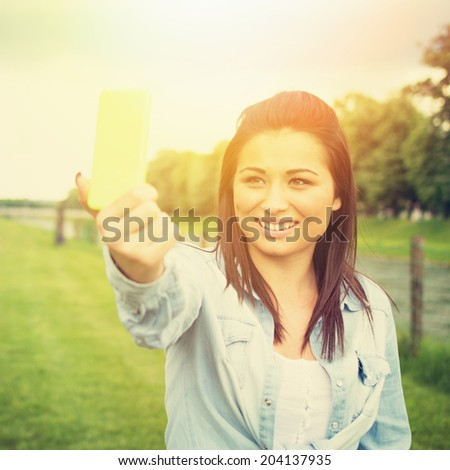 Happy young mixed race woman talking a selfie with smart phone outdoors in park on sunny summer day. Fashionable cute teenage girl photographing herself outdoors smiling wearing denim shirt. - stock photo