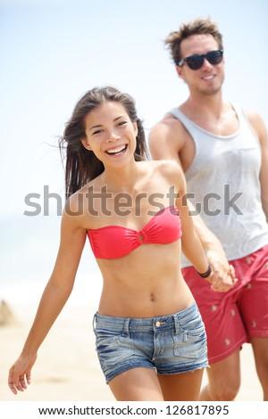 Happy young modern couple on beach. Interracial multiethnic cheerful couple walking on beach smiling joyful holding hands. Asian woman in bikini and Caucasian man. - stock photo