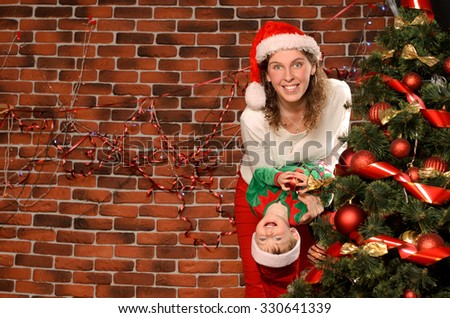 happy young mommy and her little son in festive attire playing at christmas tree indoors with space for text - stock photo