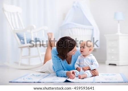 Happy young mother and adorable baby boy playing on a blue floor mat in a white sunny nursery with rocking chair and bassinet. Bedroom interior with infant crib. Mom and child on playmat at kids bed. - stock photo