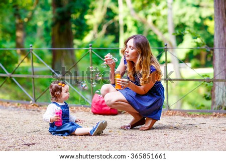 Happy young mother and adorable toddler girl blowing soap bubbles and having fun together, outdoors. Woman and daughter playing on warm sunny day in park - stock photo