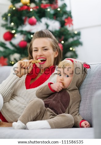 Happy young mother and baby eating cookies near Christmas tree - stock photo