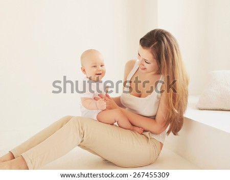 Happy young mother and baby together at home in white room near window  - stock photo