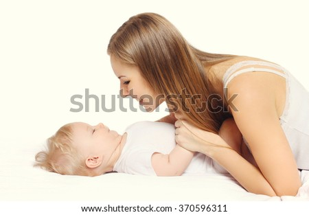 Happy young mother and baby together lying on bed - stock photo