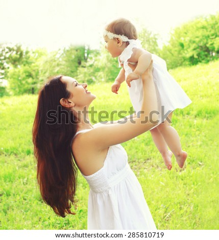 Happy young mother and baby together outdoors in sunny summer day - stock photo
