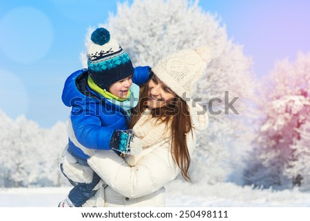 Happy young mother and child having fun outdoors in winter snowy and sunny day - stock photo