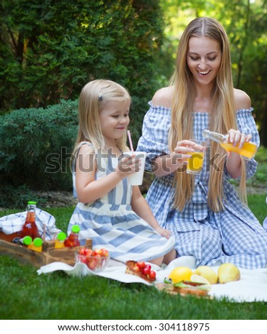 Happy young mother and daughter having picnic in summer park - stock photo