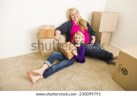 Happy Young Mother and Daughter In Empty Room With Moving Boxes. - stock photo