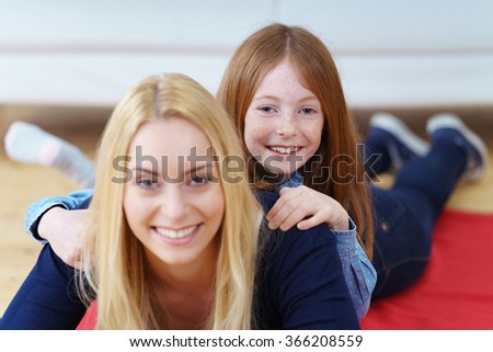 Happy young mother and daughter playing together on the floor in the living room with the young girl lying on her mothers back smiling at the camera - stock photo
