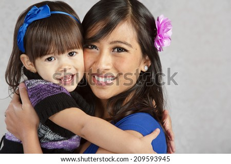 Happy young mother and female toddler hugging each other - stock photo