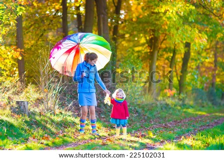 Happy young mother and her adorable toddler daughter, cute curly little girl in a colorful dress and warm coat, playing together in a beautiful autumn park enjoying a sunny fall day outdoors - stock photo