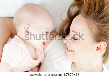 Happy young mother and her baby in bed top view