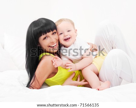 happy young mother and her baby on the bed at home - stock photo