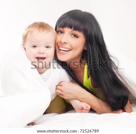 happy young mother and her baby on the bed at home (focus on the mother) - stock photo