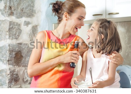 Happy young mother and her cute little daughter having fun while preparing meal in the kitchen - stock photo