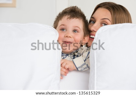 Happy young mother and her cute son playing at home - stock photo