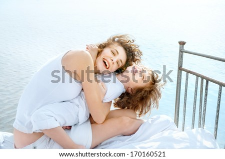 Happy young mother and her kid embrace on vintage bed against sea   - stock photo