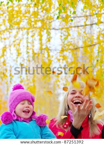 Happy young mother and her little daughter having fun in an autumn park - stock photo