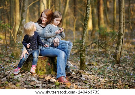 Happy young mother and her little daughters on beautiful spring day outdoors - stock photo