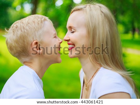 happy young mother and her nine year old son in the summer park