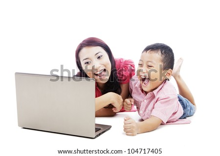Happy young mother and her son laughing with ultrabook laptop computer - stock photo
