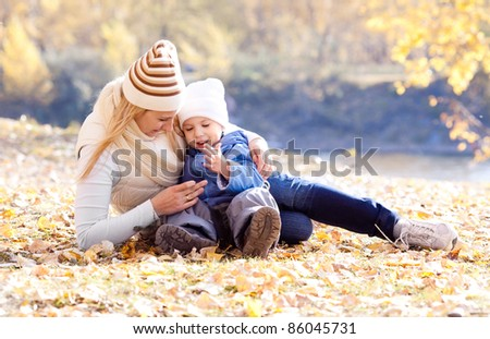 happy young mother and her son spending time outdoor in the autumn park  (focus on the woman)