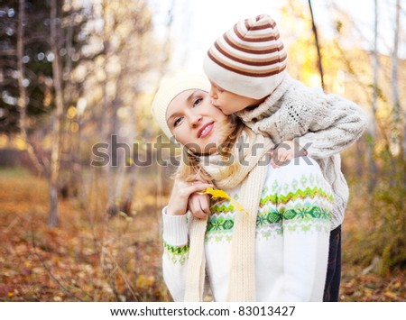 happy young mother and her son spending time outdoor in the park (focus on the woman) - stock photo