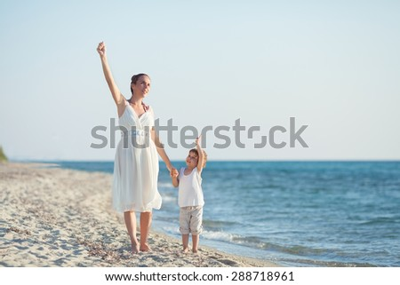 Happy young mother and her son waving to camera while walking at the beach - stock photo