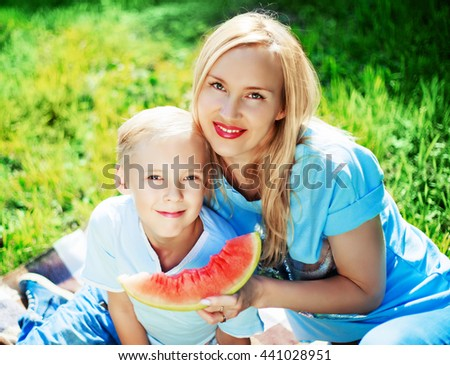 happy young mother and her ten year old son eating watermelon in the summer park - stock photo