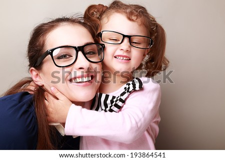Happy young mother and laughing kid in fashion glasses hugging - stock photo