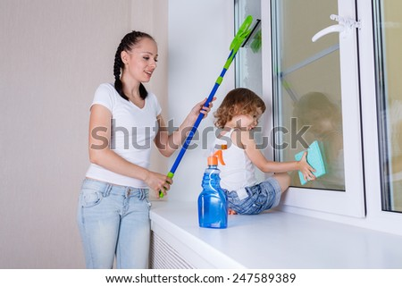 Happy young mother and little daughter cleaning windows in the house. - stock photo