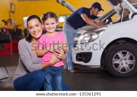 happy young mother and little daughter in garage waiting their car to be serviced - stock photo