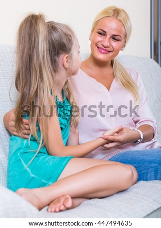 Happy young mother and little daughter talking and laughing indoors