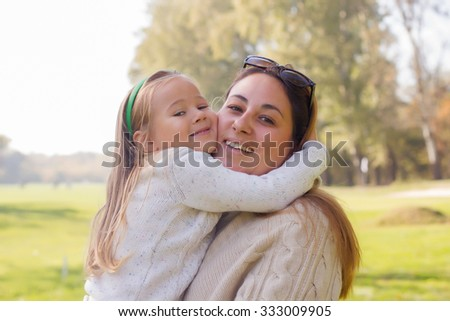Happy young mother and little girl have fun in the park. Family lifestyle, autumn season. - stock photo