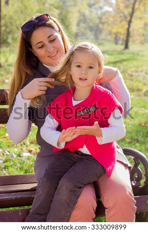 Happy young mother and little girl sitting on the bench in the park. Family lifestyle, autumn season.