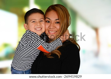 Happy young mother and son hugging and smiling - stock photo