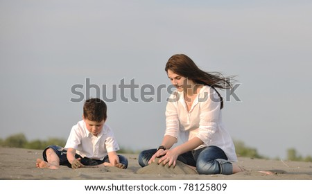 happy young mother  and son relaxing and play ind sand games on beach at summer season - stock photo