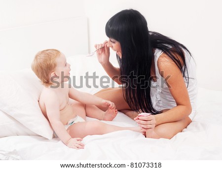 happy young mother feeding her baby with yogurt on the bed at home