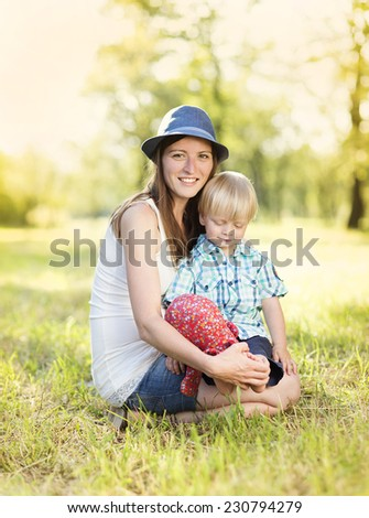 Happy young mother having fun with her little son in nature