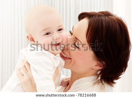 Happy young mother holding a baby boy, playing laughing having fun, healthy family concept